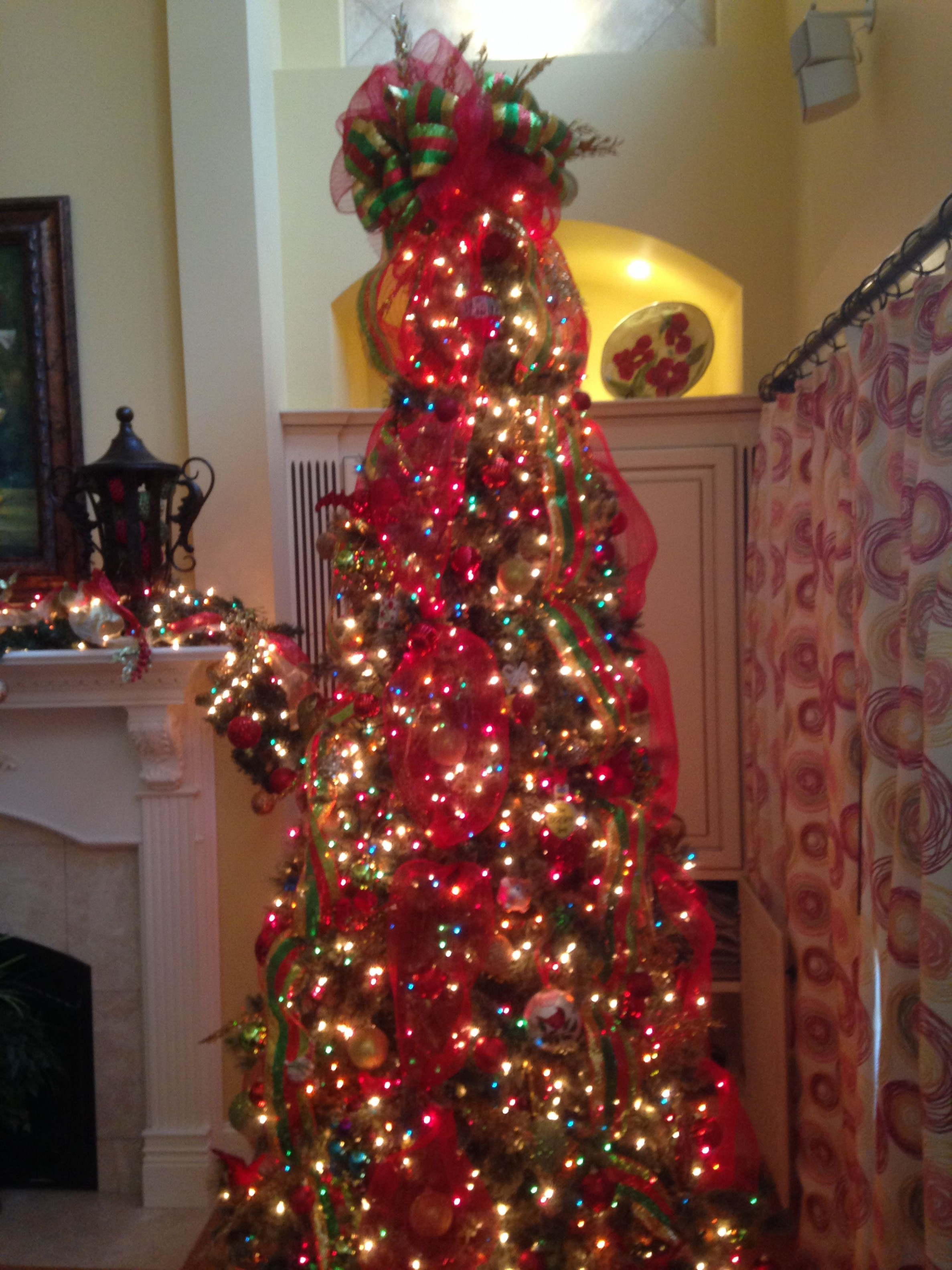 Christmas tree using clear and multi-colored lights, red mesh and ..